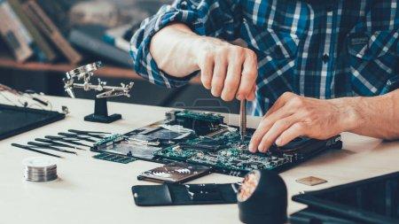Photo pour Atelier de réparation d'ordinateur. Ingénieur effectuant la maintenance d'ordinateur portable. Développeur de matériel fixant des composants électroniques. Technologie Pc - image libre de droit