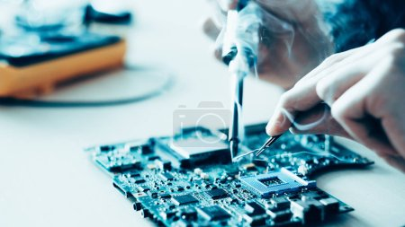 Foto de Educación en microelectrónica tecnológica. Estudiante de ingeniería aprendiendo a soldar componentes electrónicos en la placa base de la computadora . - Imagen libre de derechos