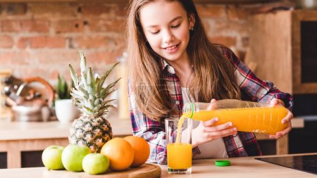 Photo for Child health and development. Vitamin orange juice for balanced nutrition. Little girl pouring fresh fruit drink from bottle. - Royalty Free Image