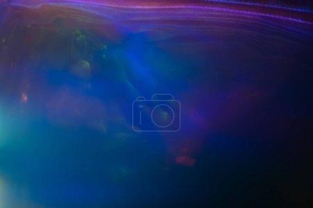 Foto de Borrosa neón multicolor líneas abstractas sobre fondo oscuro. Efecto de resplandor de la llamarada Defocused lente. - Imagen libre de derechos