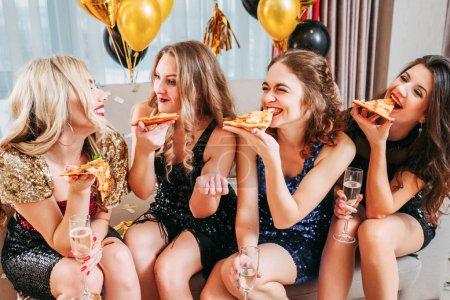 Photo pour Fête des filles. Jeunes femmes assises dans la chambre décorées de ballons, mangeant de la pizza, bavardant, souriant, s'amusant ensemble . - image libre de droit