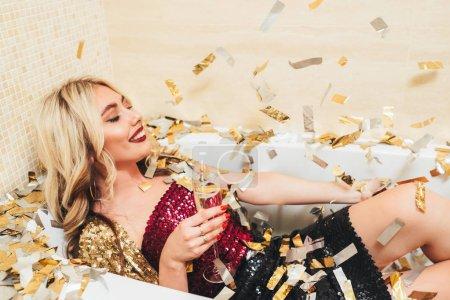 Foto de Celebración de estilo de moda de lujo. Chica rubia elegante tumbada en la bañera, sonriendo, sosteniendo copas con champán. Confeti alrededor. - Imagen libre de derechos