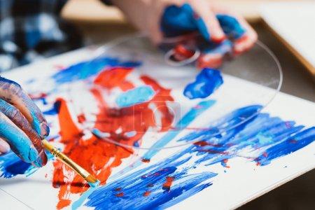 Photo pour L'art contemporain. Processus créatif. Gros plan d'une œuvre abstraite. Mains masculines tenant la palette avec peinture bleue et rouge et pinceau . - image libre de droit