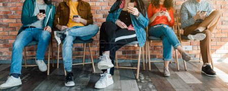 Photo for Millennials lifestyle. Group of young people sitting in modern loft office, using smartphones. Social media addiction. - Royalty Free Image