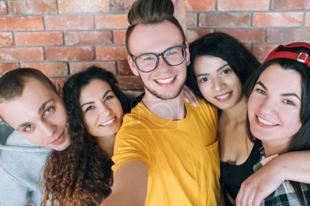 Photo for Millennials relationship, firm friendship. Hipster guy taking group selfie with coworkers. Closeup of young cheerful people. - Royalty Free Image
