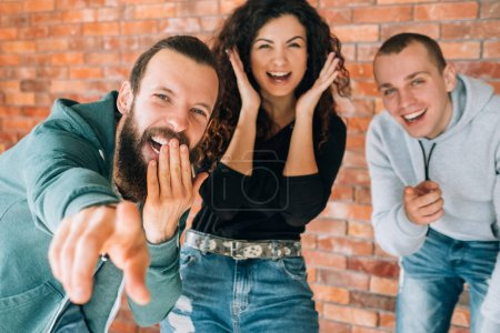 Photo for Amused, cheerful millennial mocking. Young emotional people laughing, having fun together. Hipster guy pointing finger at camera. - Royalty Free Image
