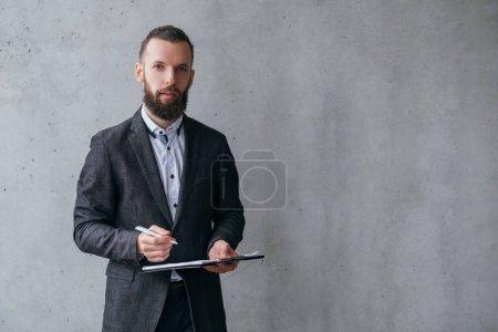 Photo pour Une carrière professionnelle réussie. Jeune homme d'affaires debout avec stylo et presse-papiers sur fond gris. Espace de copie . - image libre de droit