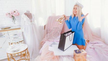 Photo pour Style de vie princesse moderne. Dame en tiare tenant de nouvelles chaussures dorées, heureux de recevoir un cadeau . - image libre de droit