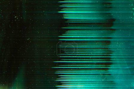 Photo pour Superposition verte poussiéreuse. Une vieille pellicule. Écarts lumineux rayures sur fond sombre . - image libre de droit