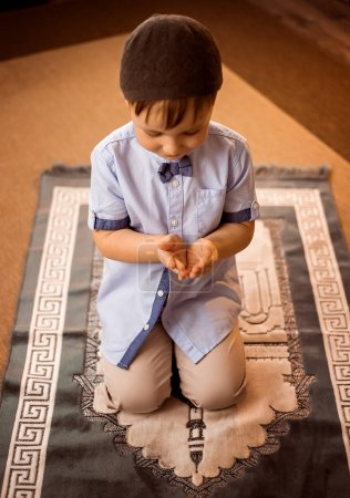 little boy praying on the rug