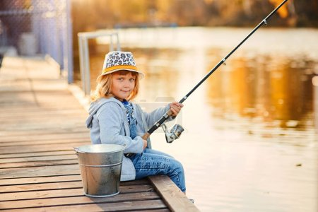 Photo for Little blond Caucasian girl sitting on a wooden pier with fishing rod. - Royalty Free Image