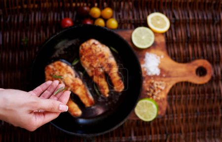 Girl salts Two red fish steak fried in a frying pan for two persons, is a pan on a wooden board close tomatoes and slices of lemon and lime