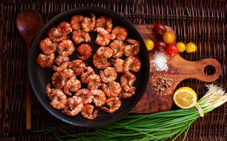 Shrimp fried in soy sauce with garlic in olive oil first press, served in a cast iron skillet, poured lemon juice,Yellow cherry tomatoes and red onions complement the composition with shrimps