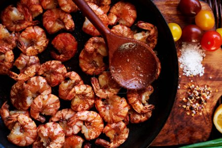 Close-up photos of colorful and appetizing,composition of the shrimp in a large black skillet, just fried over high heat in a sauce of soy sauce, garlic and olive oil, coarse salt from the sea, spices