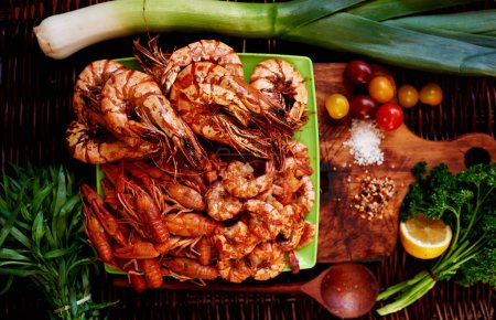 On the bright green plate lined with a great appetizer to any table, shrimp, prawns, tiger prawns, crabs, lie next to a slice of lemon, you can add them to taste for seafood