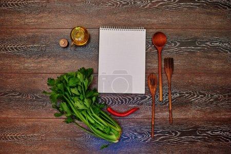 A place for advertising, notebook lying on a wooden table next to the kitchen, wooden cutlery, olive oil, red hot chili peppers