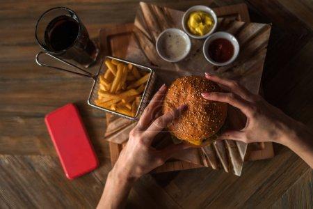 Foto de Mujer tiene hamburguesa con las manos y fritas en el fondo de café. Burger fresco cocinado en barbacoa en papel artesanal. Comida americana. Gran hamburguesa con carne y verduras de primer plano desenfocado en el fondo - Imagen libre de derechos