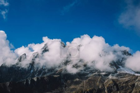 High mountains with snowy peaks in clouds with blue sky. Colorful landscape with beautiful rocks and dramatic cloudy sky. Nature background. Amazing mountains. Travel concept. Everest region, Nepal.