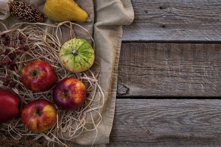 Autumn background with ears of wheat, red apples, corn and pumpkins. Fall harvest on aged wood with copy space. Mockup for seasonal offers and holiday post card, top view. Toned image.