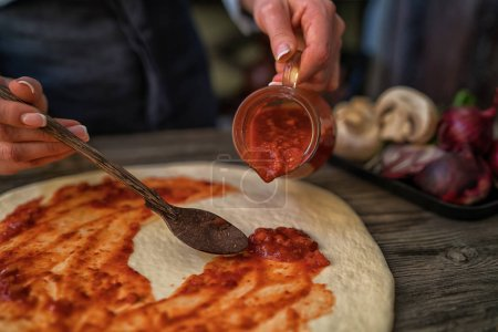 The process of making pizza. Prepare dough hand topping. Woman hand is spreading pasteurized tomato paste onto a pizza base. Food concept. Preparing traditional italian pizza. Toned image.