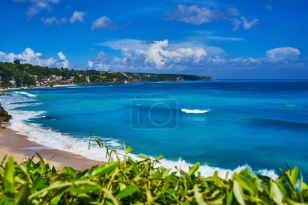 Travel, tourism and vacations concept. Beautiful and bright ocean water on a tropical beach location for the holiday season. Paradise blue seascape. Tropical island with beach, sea and green plants