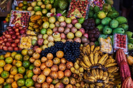 Asian exotic fruits. Market stall with variety of organic fruits. Colorful fruits in the marketplace. Bright summer background. Healthy, organic food. Natural nutrition for diet. Selective focus.