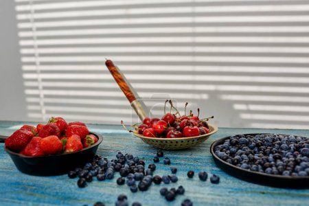 Photo for Cook resigned in different pans berries, strawberries, cherries and blueberries to prepare one delicious toppings for bagels - Royalty Free Image