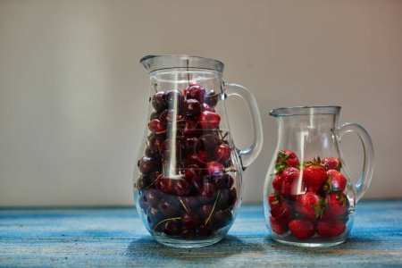 On a white background are two transparent glass carafe with cherries, strawberries