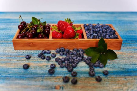 On the table lies a blue vintage wooden form with individual cells for a variety of sweets and fruits, cook it spread fresh ripe blueberries, strawberries and cherries