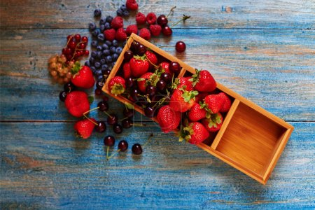 Photo for Simple ideas for serving desserts, the chef put the berries in a wooden box with individual cells - Royalty Free Image