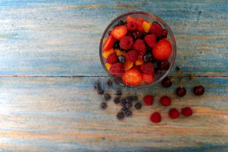 Top view on a vintage wooden desk with peeling paint, there is a deep glass bowl with fresh chopped salad of ripe berries