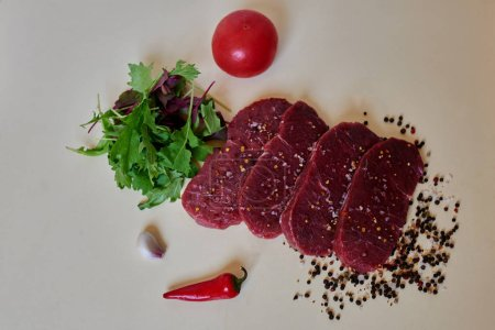 On a white table a smooth, fresh meat is cut into steaks next to fresh vegetables from the buyout will be made salad