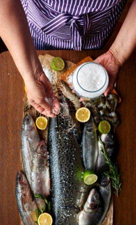 Photo pour Main femme salé poisson et marinade faite maison, ménagère, préparer le dîner pour une famille nombreuse - image libre de droit