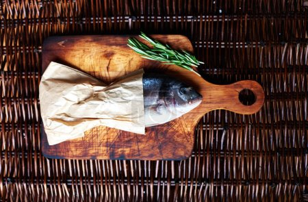 Seller fishmongers packed fresh fish in paper. Fresh fish wrapped in brown paper lying on a cutting board