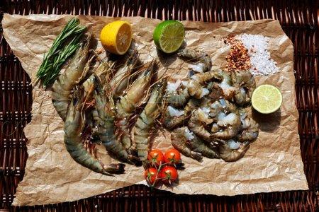 Photo pour Les crevettes sont sur le papier parchemin brun clair coupé pour fermer les deux moitiés de citron vert et citron - image libre de droit