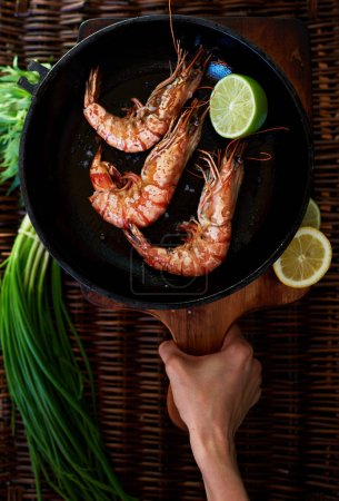 Photo for Waitress fish restaurant prepares to issue customers with prawns, fresh seafood are served with lime and green onion, Tiger shrimps fried on a grill in a deep cast iron skillet - Royalty Free Image