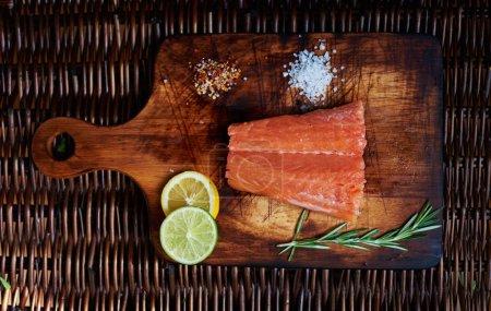 Photo pour Chef prêt à décaper steak de saumon frais. Un petit morceau de saumon est sur la planche pour couper la viande et le poisson est dispersé à côté du sel et du poivre - image libre de droit