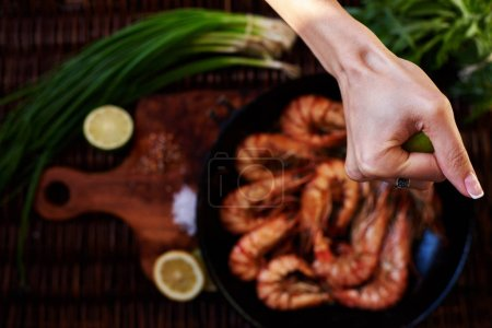 Photo for Waitress fish restaurant prepares to issue customers with prawns, fresh seafood are served with lime and green onion, Tiger shrimps fried on a grill in a deep cast iron skille - Royalty Free Image