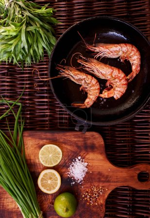 The best snack to beer, prawns, grilled or rapid fire in a deep frying pan. Three large tiger shrimps lie in a deep bowl for dikustatsii near lemon and lime and rosemary