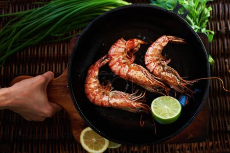 Photo for A young girl carries snacks on the table, it's Tiger prawns fried quickly over high heat in a cast iron frying pan and poured on top of a lemon - Royalty Free Image