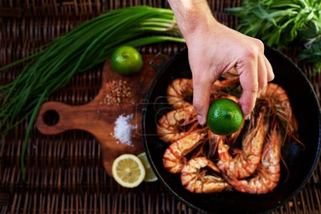 Photo for In the foreground, a man's hand squeezes a lemon on fried tiger prawns, situated near the green onion bunch of rosemary, In the old cast iron skovordke The royal fried shrimp - Royalty Free Image