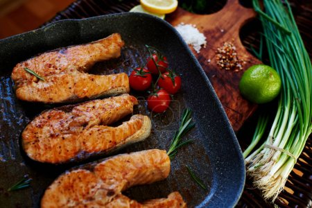 Photo for Wife waits for guests to cook for dinner salmon steaks,Fish steaks are on the grill pan with rosemary and tomatoes,On a wooden board with a pan put the fried fish - Royalty Free Image