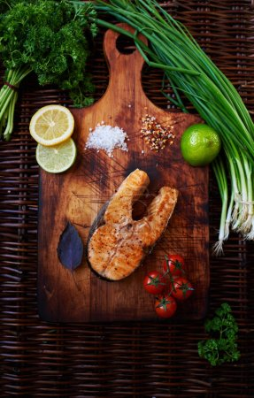 Big salmon steak baked in the oven until golden brown lying on a wooden surface, for serving fish perfect tomatoes chives and lemon, cook restaurant cooked piece of salmon on the grill