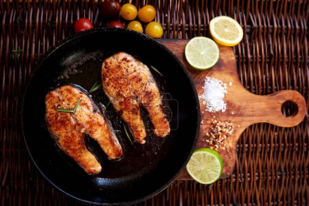 Steaks of red fish grilled for two people, is a pan on a wooden board close tomatoes and slices of lemon and lime