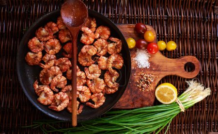 The composition of the shrimp in a large black skillet, just fried over high heat in a large sauce with sea salt, spices.