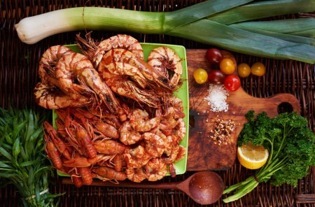 Cook fish restaurant has prepared a snack for beer, shrimp Royal, Tiger prawns, crabs, all laid out on a bright contrast dish served with lemon wedges, cherry tomatoes and parey for fresh spring salad