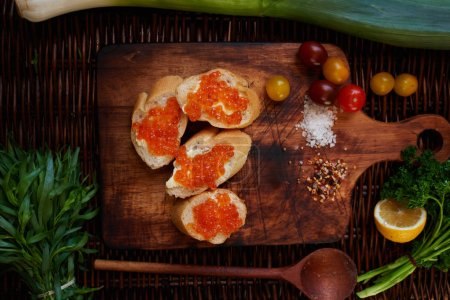 Photo for Sandwiches with red caviar, good wholesome breakfast for the entire family, in white crispy baguette buttered salted red caviar on top, served with all the cherry tomatoes - Royalty Free Image