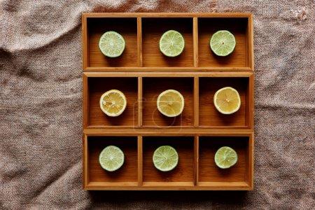 Foto de Y limón cortan en rebanadas y puesto en tamaño en forma cuadrada de madera con una celda para cada lóbulo - Imagen libre de derechos