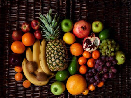 plenty of fruit picked in bright composite fruits lie on a dark wicker table, Vitamin charge for each day the most delicious and healthy fruit
