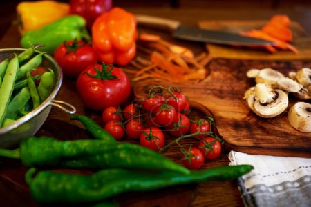 Photo for Tomatoes, red peppers, chili pepper lie on a chopping board, a knife lying nearby, in an aluminum bowl are just washed peas - Royalty Free Image